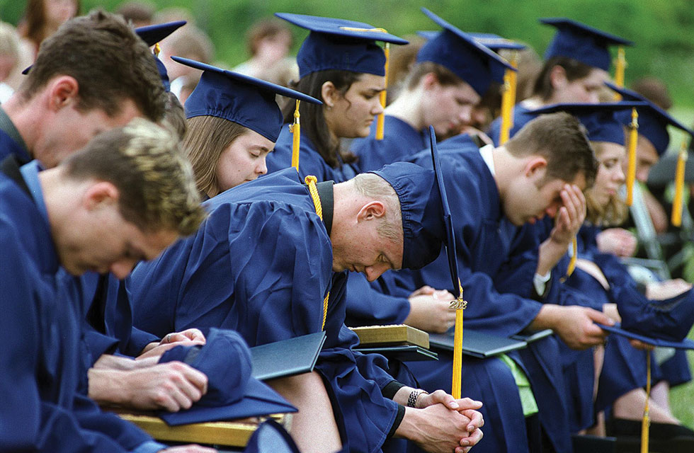 Students in blue cap and gowns with heads bowed