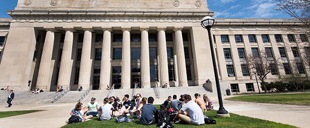 Students sitting on lawn outside Angell Hall University of Michigan