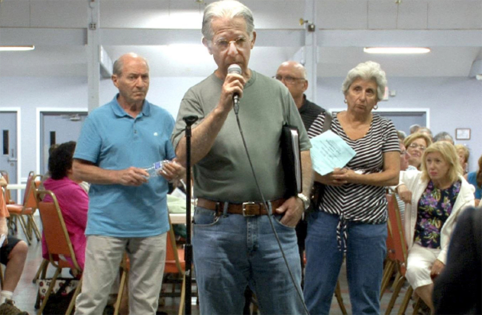 people at a public meeting using microphone
