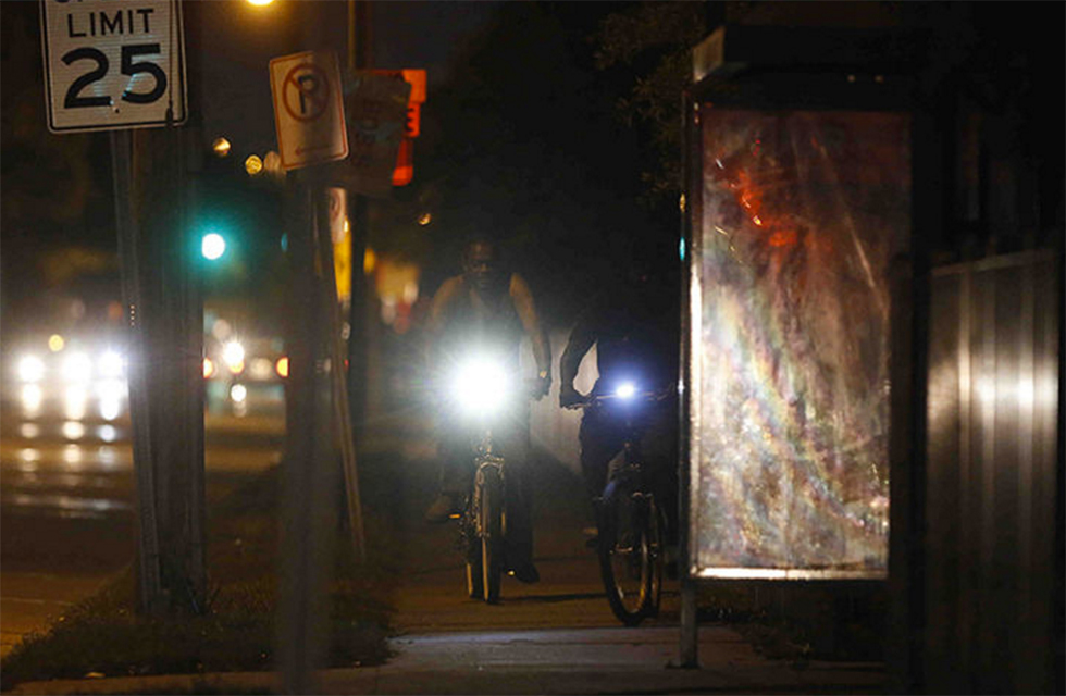 Bicyclists ride at night along Main Street in West Tampa